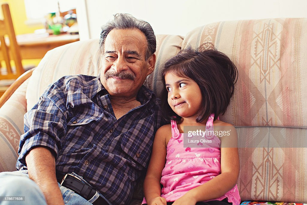 Grandfather and Granddaughter Laughing on Couch : Stock Photo