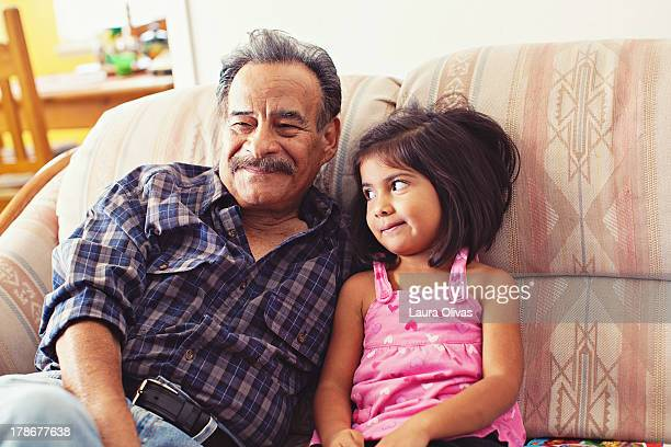grandfather and granddaughter laughing on couch - latino américain photos et images de collection