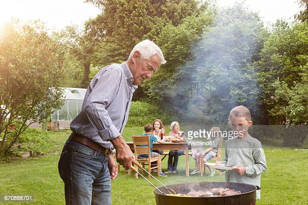 Grandfather and granddaughter on a family barbecue