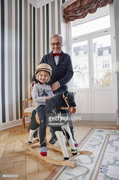 Grandfather and granddaughter on rocking horse