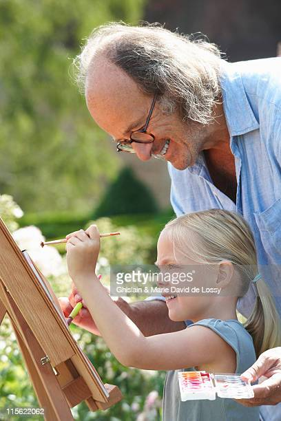 Grandfather and granddaughter painting