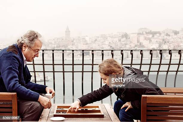 grandfather and granddaughter playing backgammon - backgammon stock pictures, royalty-free photos & images