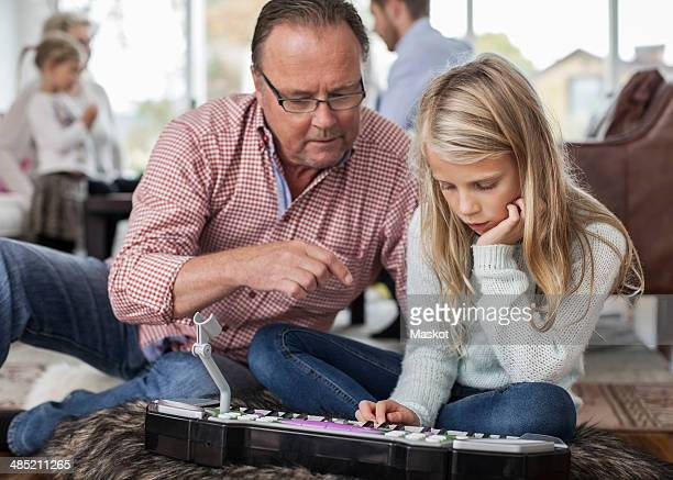 Grandfather and granddaughter playing piano with family in background at home