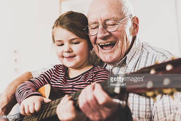 grandfather and granddaughter playing together guitar - grandfather stock pictures, royalty-free photos & images