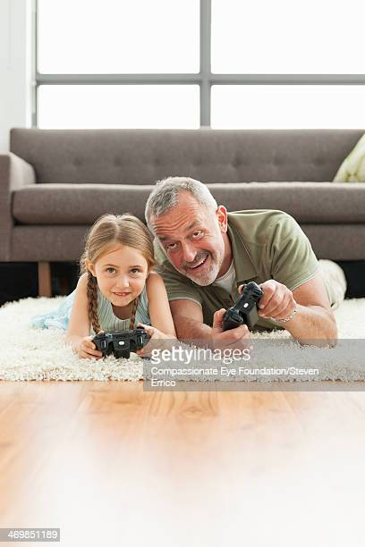 Grandfather and granddaughter playing video games