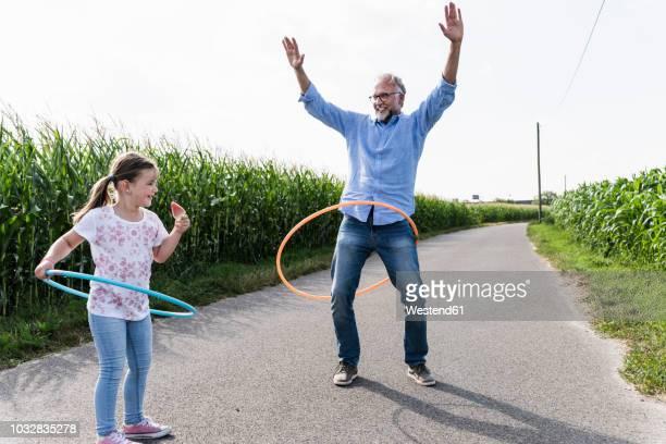 grandfather and granddaughter playing with hoola hoop in the street - bewegungsaktivität stock-fotos und bilder