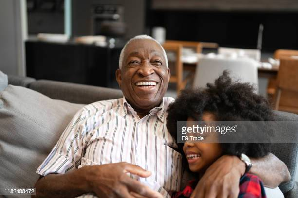 grandfather and granddaughter playing with smartphone - grandfather stock pictures, royalty-free photos & images