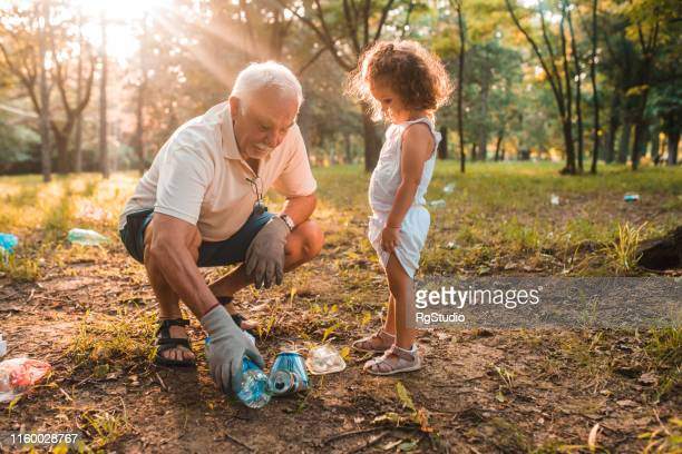 grandfather and granddaughter recycling - inquinamento ambientale foto e immagini stock