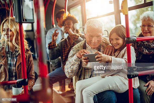 Grandfather and granddaughter riding in a bus