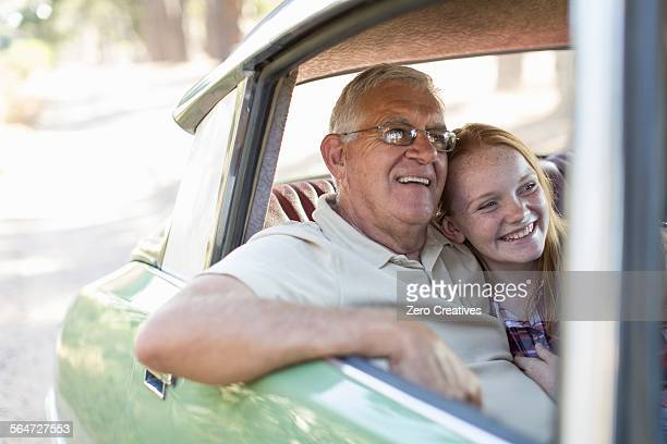 Grandfather and granddaughter sitting in back seat of car, smiling