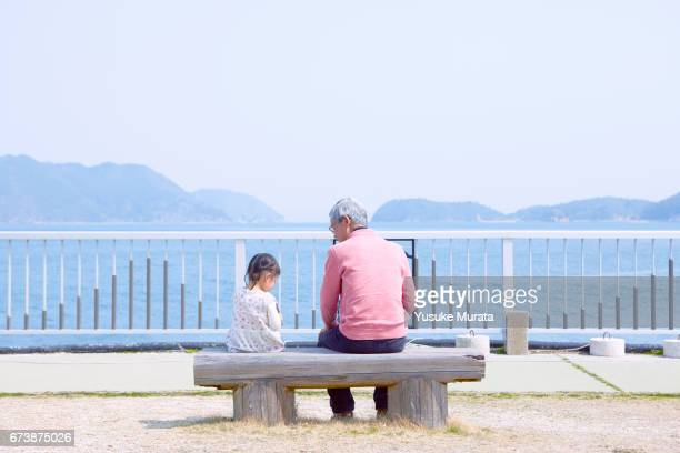 grandfather and granddaughter sitting on chair - ベンチ ストックフォトと画像
