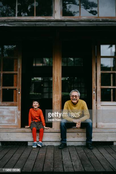 grandfather and granddaughter sitting on patio and looking at camera - ippei naoi stock pictures, royalty-free photos & images