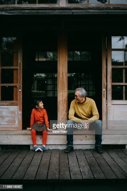 grandfather and granddaughter sitting on patio and smiling at each other - ippei naoi stock pictures, royalty-free photos & images
