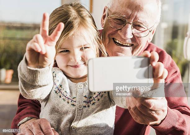 Grandfather and granddaughter taking selfies with a smart phone