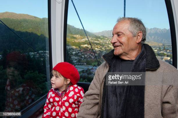 grandfather and granddaughter traveling by aerial tramway - rafael ben ari bildbanksfoton och bilder