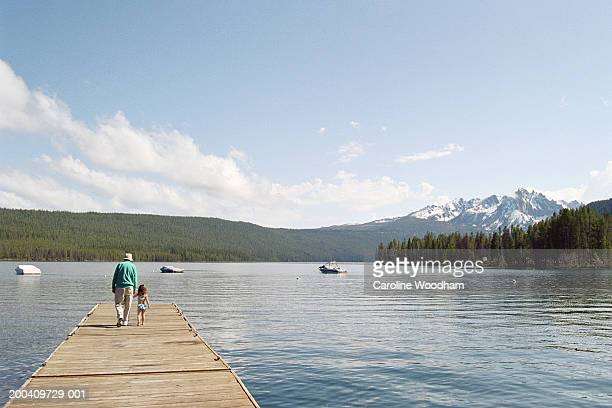grandfather and granddaughter (2-4) walking on lake jetty, rear view - mid distance stock pictures, royalty-free photos & images
