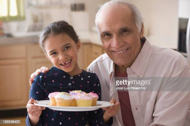 Grandfather and granddaughter with cupcakes