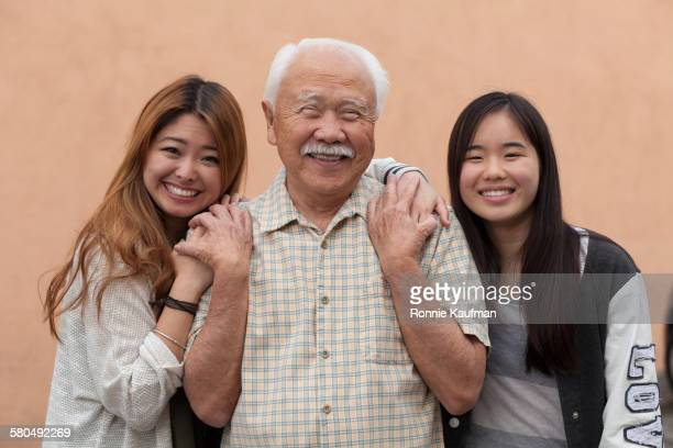 Grandfather and granddaughters smiling outdoors