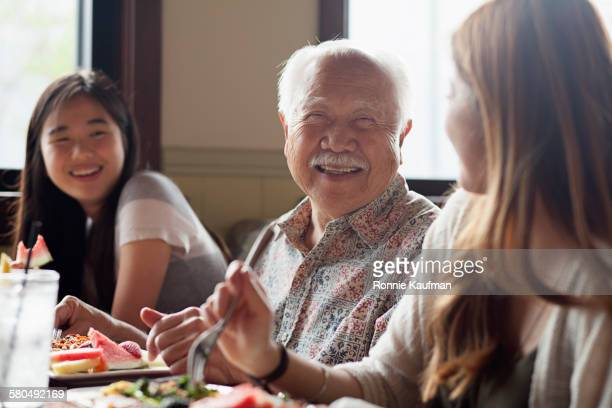 Grandfather and granddaughters talking in restaurant booth