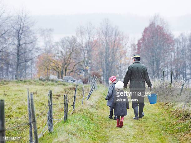 Grandfather and granddaughters walking on footpath
