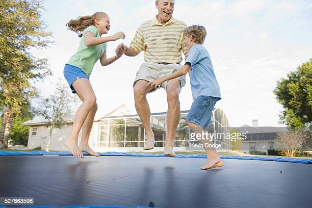 Grandfather and Grandkids Jumping on Trampoline