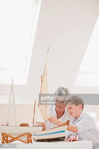 Grandfather and grandson assembling model sailboat