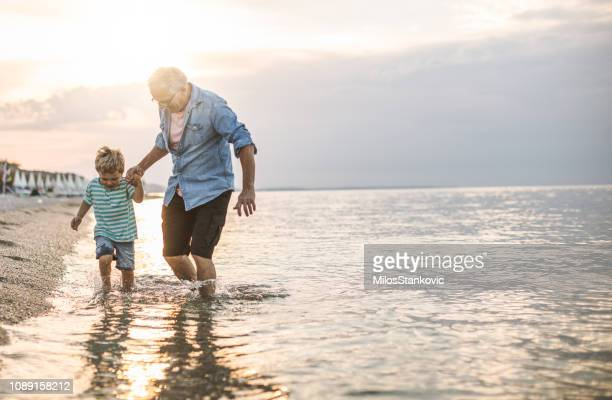 grandfather and grandson at the beach - grandfather stock pictures, royalty-free photos & images