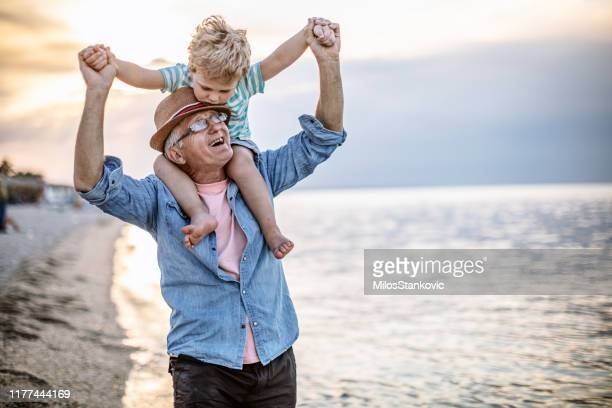 grandfather and grandson at the beach - water's edge stock pictures, royalty-free photos & images