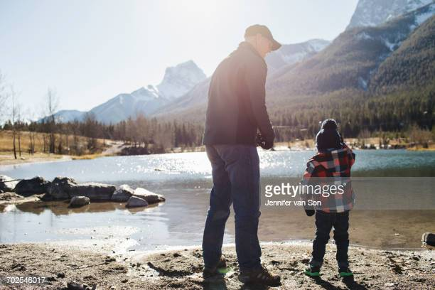 Grandfather and grandson beside river, rear view, Rocky Mountains, Canmore, Alberta, Canada