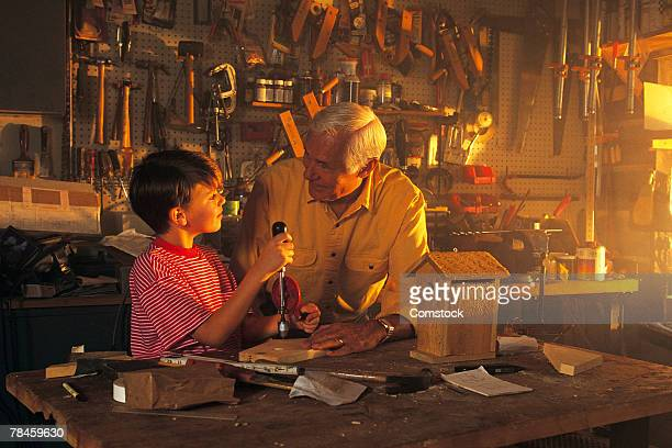 Grandfather and grandson building a birdhouse