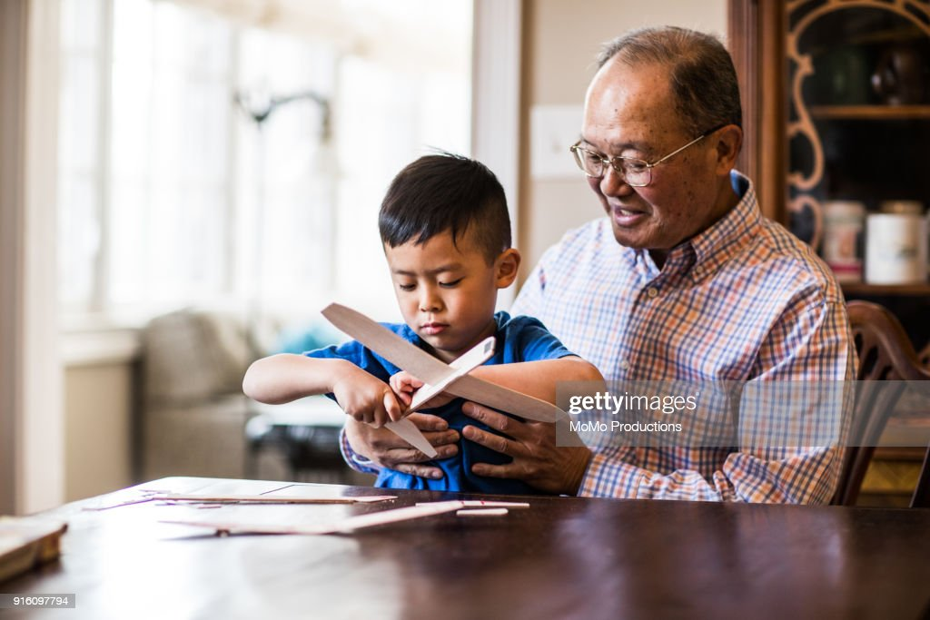Grandfather and grandson building model airplane : Stock Photo