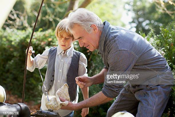 grandfather and grandson catching fish with fishing rod - oil change stock pictures, royalty-free photos & images