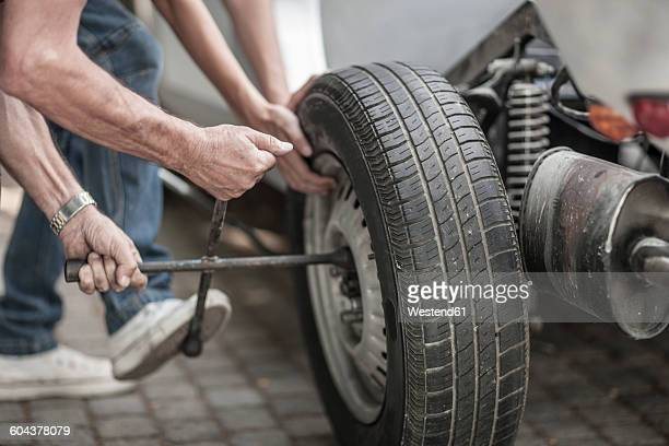 Grandfather and grandson changing car tire