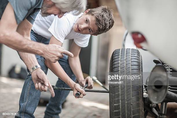 grandfather and grandson changing car tire - flat tire stock pictures, royalty-free photos & images