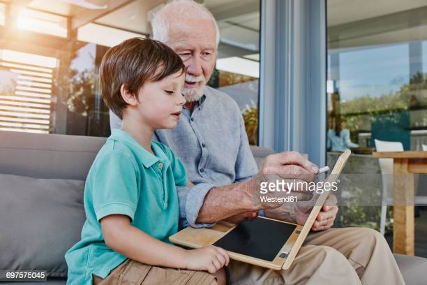 Grandfather and grandson drawing on laptop-shaped blackboard