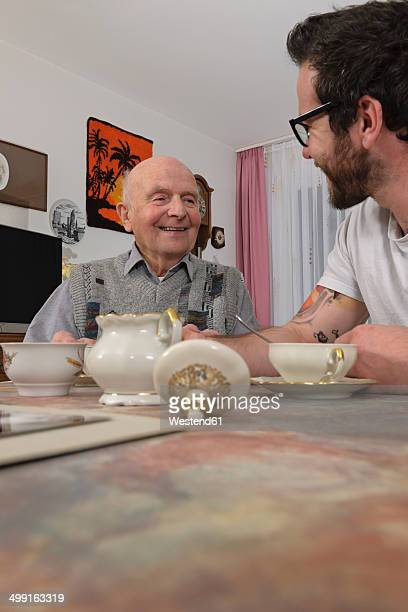 grandfather and grandson drinking coffee at home - sugar bowl crockery stock photos and pictures