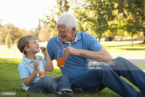 Grandfather and grandson drinking through straw eyeglasses