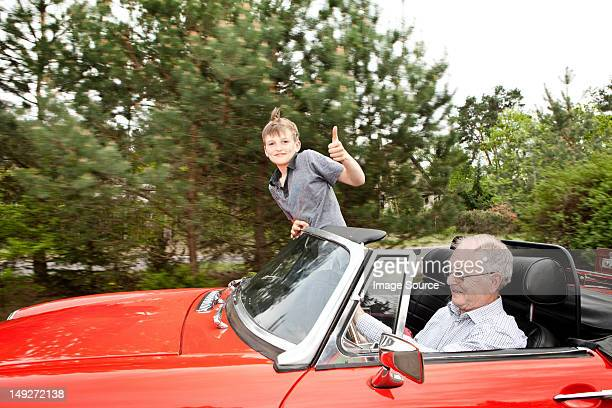 Grandfather and grandson driving in vintage car