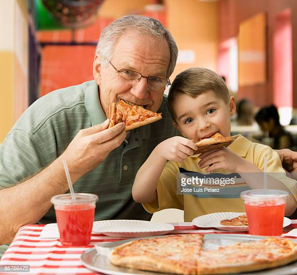 Grandfather and grandson eating pizza