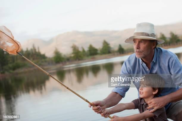 Grandfather and grandson fishing at lake