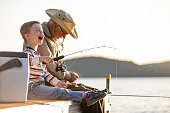 Grandfather and Grandson Fishing At Sunset in Summer