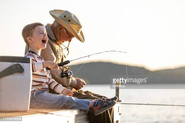 grandfather and grandson fishing at sunset in summer - enjoyment stock pictures, royalty-free photos & images