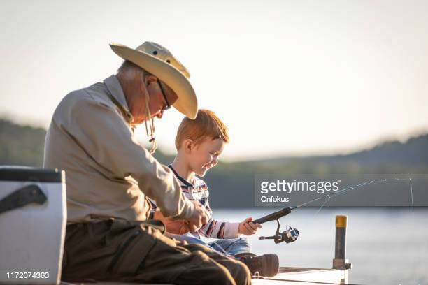 grandfather and grandson fishing at sunset in summer - older redhead stock pictures, royalty-free photos & images
