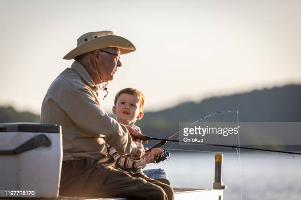 grandfather and grandson fishing at sunset in summer - estilo de vida ativo imagens e fotografias de stock