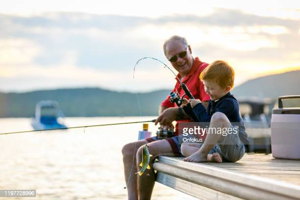 grandfather and grandson fishing at sunset in summer - fishing stock pictures, royalty-free photos & images