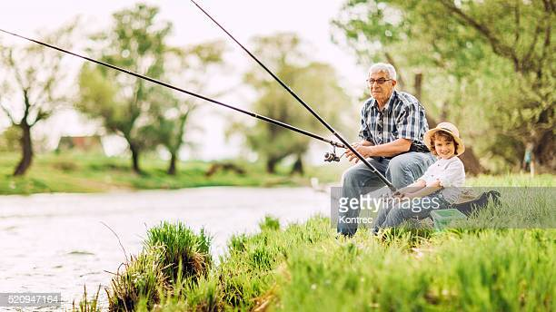 Grandfather and grandson fishing by the river