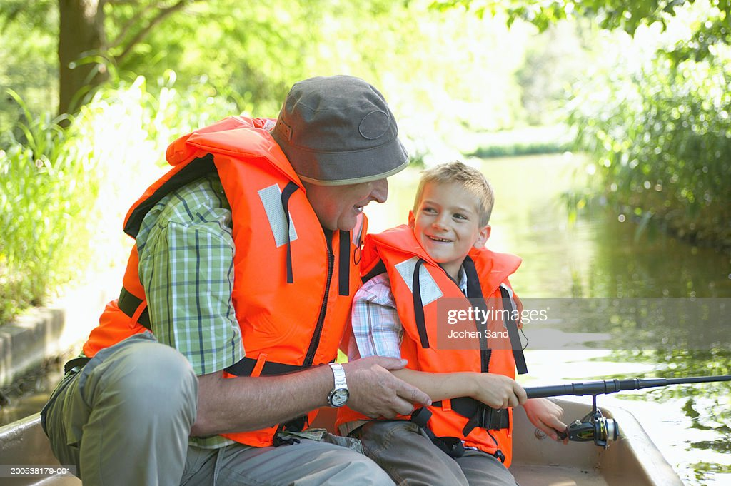 Grandfather and grandson (6-8) fishing from boat, smiling : Stock Photo