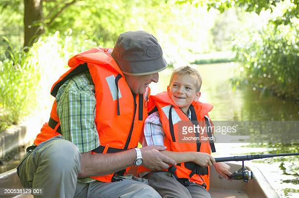 grandfather and grandson (6-8) fishing from boat, smiling - life jacket stock pictures, royalty-free photos & images