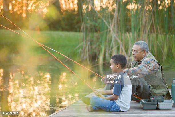 grandfather and grandson fishing on pier - nature stock pictures, royalty-free photos & images