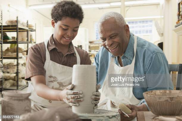 Grandfather and grandson forming pottery on wheel in studio